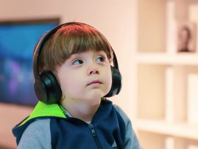 Little boy with special needs using headphones staring upwards