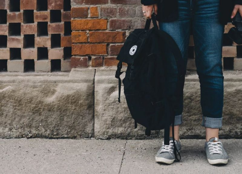 Student's legs wearing jeans holding black bag on street