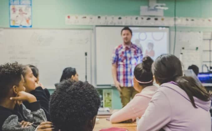 Teacher standing in front of pupils in classroom setting