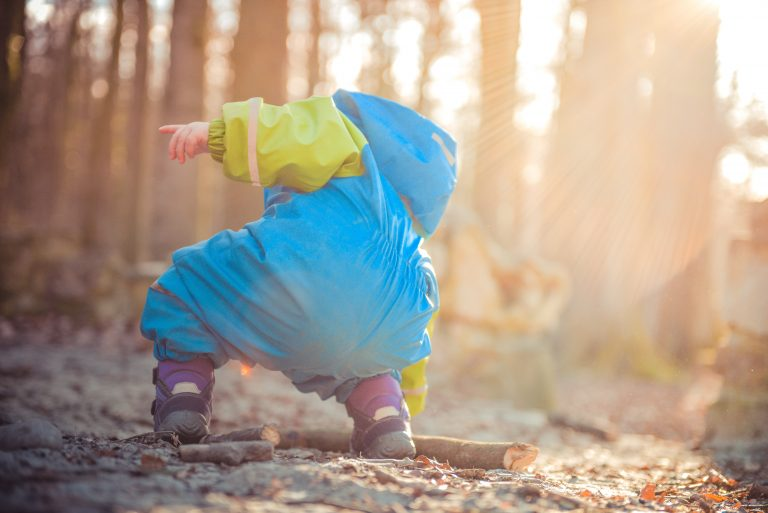 Toddler playing in the woods