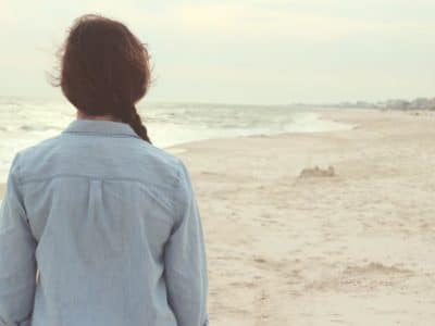 Young woman with plait hair with her back to you standing on the beach looking at the sand and sea