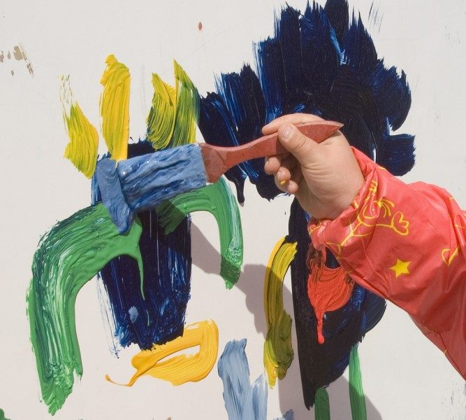 Child's hand painting on a wall with coloured paints