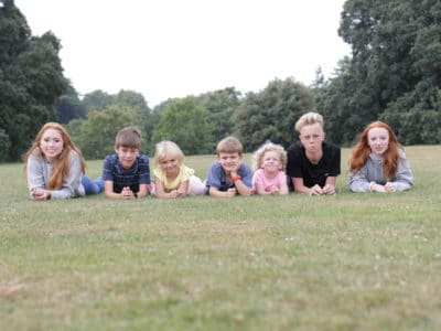 Seven Fostering Devon children - three teens and four school age -laying on grass facing towards the camera