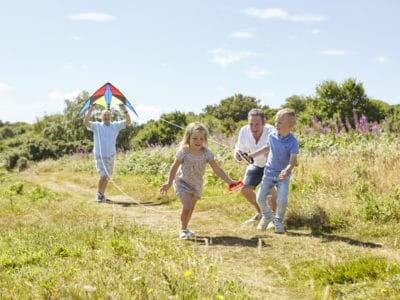 Adoptive male parents running with a kite and playing with their primary school age children on a Devon path, on a sunny day