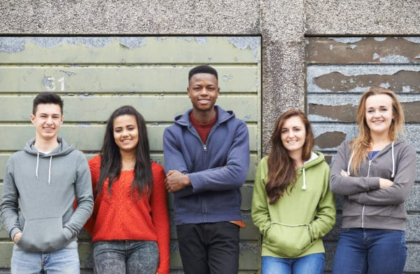 five teenagers standing in front of a wall