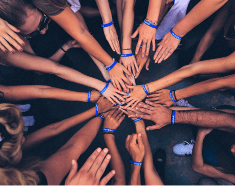 Looking down on a group of people in circle each with a hand placed into the middle