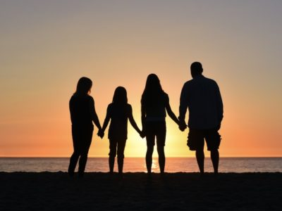 a family of four silhouetted against a sunset