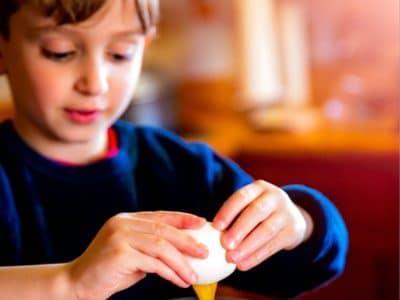 a boy cracking an egg
