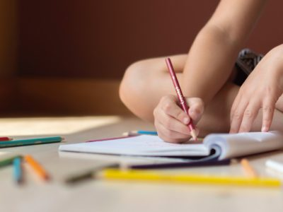 a person writing in book surrounded by pencil crayons