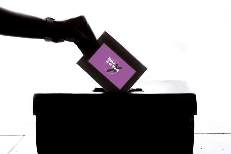 a hand placing a vote into a ballot box