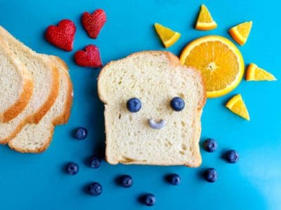 a slice of bread with a smiley face made out of blueberries