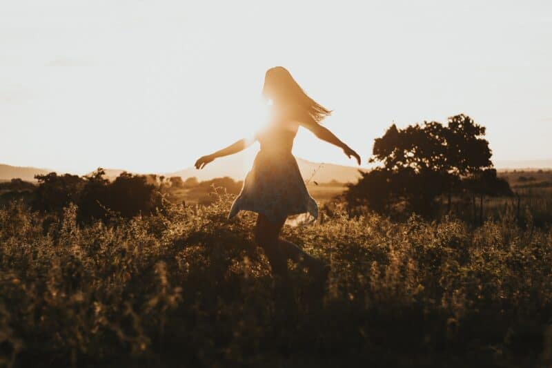 a woman skipping through a field at sunset