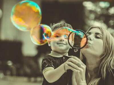 a mother and child blowing bubbles